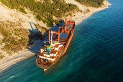 Aerial view of cargo ship run aground on wild coast, shipwreck after storm, drone shot