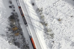 Aerial view of cargo train wagons, a double-track railway. Winter rail road with white snow, top view. Transport infrastructure, train track, snowy landscape