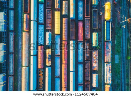 Aerial view of cargo trains. Railway wagons with goods on railroad. Top view of colorful freight train on the railway station. Heavy industry. Industrial conceptual landscape. Transportation. Art