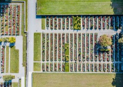 Aerial view of cemetery with graves in regular pattern and green lawn