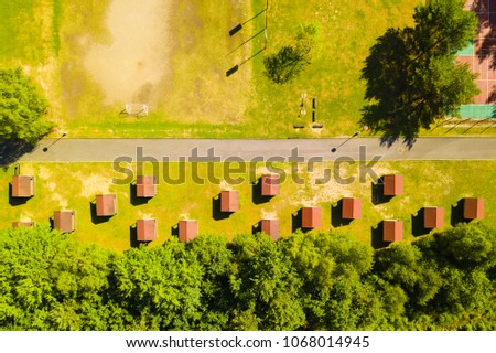 Aerial view of children summer camp site and recreational area near forest. Drone view of many holiday cottages. Background texture concept.