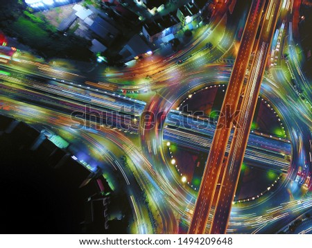 Aerial view of circle road traffic in roundabout and highway at night, Expressway, Modern transportation, Multilevel junction highway, Important infrastructure of transport, Top view.