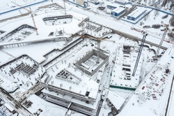 aerial view of city construction site with working cranes in winter time