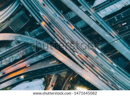 Aerial view of city landscape with autobahn motorway in metropolis, Bird's eye evening view. automobiles moving at street with modern automotive expressway. interchange road highway, junctions freeway