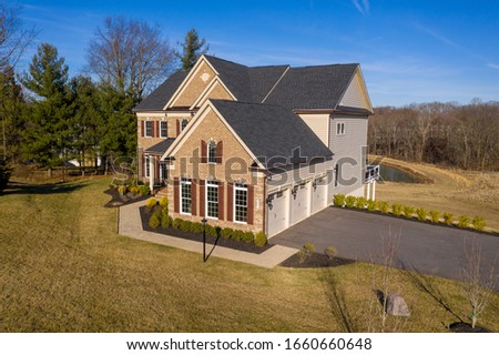 Aerial view of classic colonial luxury estate home in Maryland w/ brick facade, double hung sash windows with shutters, asphalt single roof, double peak gable, metal roof covered porch, curb appeal