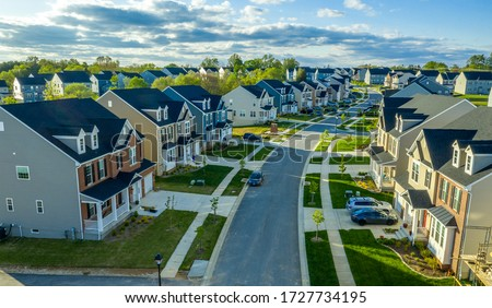 Aerial view of classic upper middle class neighborhood street with luxury single family homes with colorful siding for the up and coming with trees planted at equal distance in Maryland USA