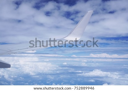 Aerial view of cloud and sky and land with airplane wing from airplane window ,Traveling concept. #752889946