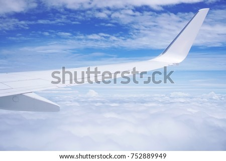 Aerial view of cloud and sky and land with airplane wing from airplane window ,Traveling concept. #752889949