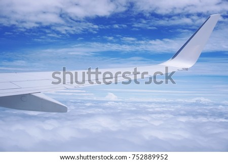 Aerial view of cloud and sky and land with airplane wing from airplane window ,Traveling concept. #752889952