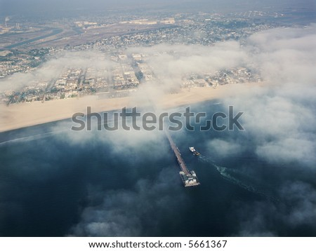 Aerial view of clouds covering beachfront and fishing pier in southern California.