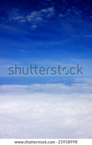 Aerial view of cloudy blue sky from aircraft window.
