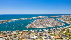 Aerial view of coastal homes in Newport Beach harbor, Orange County, California on a sunny day with boats in the water with Balboa Island and Peninsula visible.