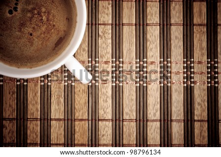 Aerial view of coffee cup with copy-pace on the tablecloth