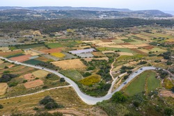 Aerial view of colorful agriculture fields and road. Nature countryside landscape. Malta country