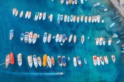 Aerial view of colorful boats and yachts in port in blue sea at sunset. Summer landscape with beautiful motorboats in harbor, pier, transparent water in Dubrovnik. View from above of harbour. Travel