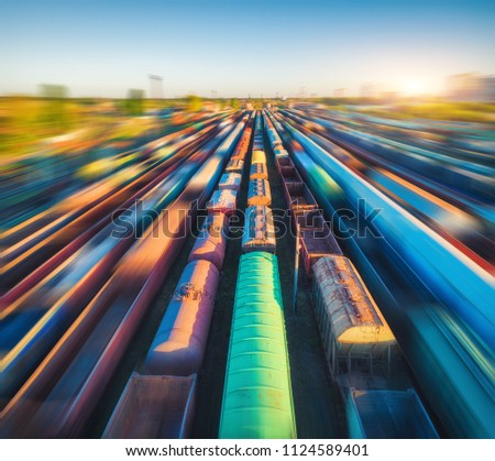 Aerial view of colorful freight trains at sunset. Cargo wagons with goods on railway station. Railroad. Heavy industry. Industrial landscape with railway platform. Top view from drone of depot. Urban