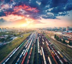 Aerial view of colorful freight trains. Railway station. Wagons with goods on railroad. Cargo trains. Heavy industry. Industrial scene with trains, city buildings and cloudy sky at sunset. Top view