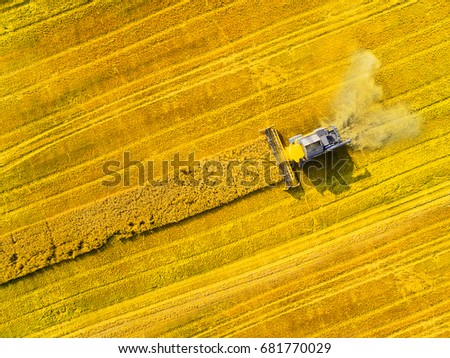 Aerial view of combine harvester. Harvest of rapeseed field. Industrial background on agricultural theme. Biofuel production from above. Agriculture and environment in European Union.  - Shutterstock ID 681770029