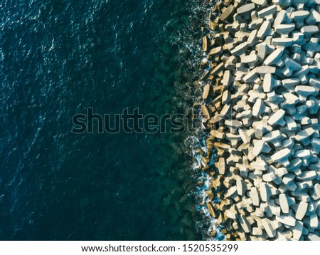 Aerial view of concrete sea fortification texture. Breakwaters. Sea city beach with breakwaters. Blue ocean. Drone #1520535299