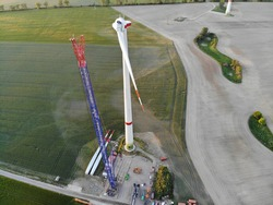 Aerial view of construction site of a wind turbine with crane on pasture in rural area at sunset.