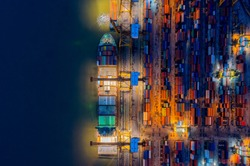 Aerial view of Containers yard shot from drone in port congestion with ship vessels are loading and discharging operations of the transportation in international port.Shot from drone.