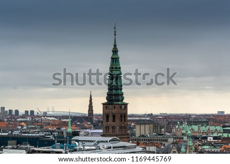 Aerial view of Copenhagen City from the The Round Tower (Rundetaarn) in rainy misty day with cloudy sky and building of Saint Nikolas church bell tower, Now is Copenhagen Contemporary Art Center #1169445769
