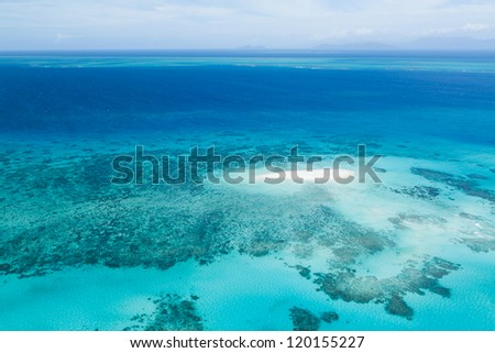 Aerial view of coral sand cay and Great Barrier Reef with clear blue water, Queensland, Australia