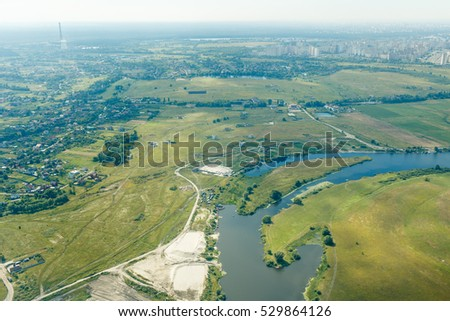 Aerial view of countryside with river near a big city