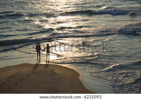 Aerial view of couple holding hands on beach in Bald Head Island, North Carolina at sunset.