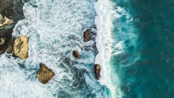 Aerial view of crashing waves on rocks. View from above, drone photo, beautiful nature background