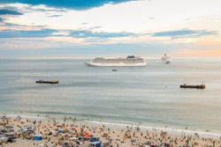 Aerial view of crowded beach with two large cruise ships on the horizon at sunset.