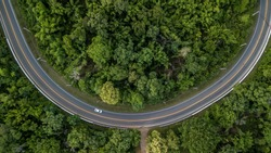 Aerial view of curve green forest road at South East Asia, Aerial view of a provincial asphalt street road adventure passing through a forest with car, Thailand.