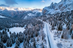 Aerial view of Curved road in the snowy mountains of Italian Alps in South Tyrol with dolomites in background / Sunny winter day with harsh shadows and lot of snow