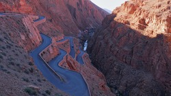 Aerial view of curvy serpentine road at a narrow passage of famous Dadès Gorges in the southern Atlas Mountains near Boumalne Dadès, Morocco, Africa in the shadow of the bright morning light.