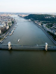 Aerial view of Danube river in Budapest city. Hungary Europe. Bridges, river bifurcates. Summer. Blue sky. Nature. Water transport, boats and ferries moored near riverside.