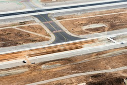 Aerial view of development construction in taxiway and runway in an international airport. Asphalt and concrete material for infrastructure and expansion work.