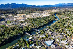 Aerial view of downtown Grants Pass with the Caveman concrete arch bridge and the 7th street bridge crossing the Rogue River