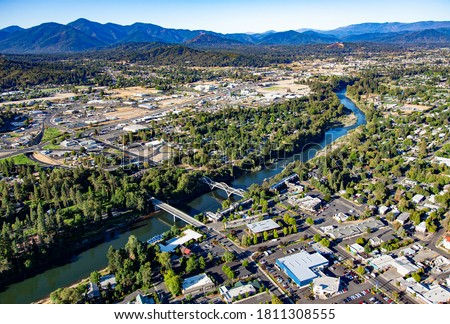 Photo of  Aerial view of downtown Grants Pass with the Caveman concrete arch bridge and the 7th street bridge crossing the Rogue River