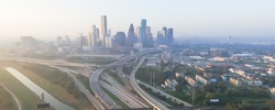 Aerial view of Downtown Houston with Interstate Highway I-10 and I-45 in early foggy fall morning. Seen from Northeast side. Panorama style.