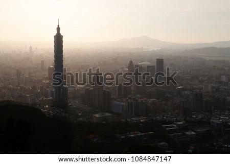 Aerial view of Downtown Taipei, capital city of Taiwan, on a hazy dusky afternoon with prominent Taipei 101 Tower amid skyscrapers in Xinyi District, mountain & river silhouettes in distant background