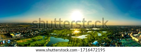 Aerial view of dramatic sunset or sunrise and colorful sky over golf field Bangkok Thailand. bird eye view over Golf course in the tropical Bangkok city skyline and beautiful colorful clouds sky.