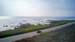 Aerial view of driving in a Ford Mustang convertible down the ocean road in California near the Pigeon Point lighthouse.