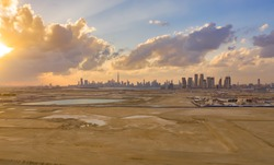 Aerial view of Dubai Downtown skyline with desert sand, United Arab Emirates or UAE. Financial district and business area in smart urban city. Skyscraper and high-rise buildings at sunset.