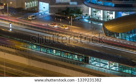 Aerial view of Dubai Tram in Dubai marina night timelapse. Dubai Tram runs in a loop around Marina and JBR area and links up with the Dubai Metro and the Palm Monorail.
