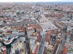 Aerial view of Duomo di Milano Cathedral in Duomo Square. Gothic cathedral in the center of Milan. Drone view of the gallery and Milano rooftops, in north Italy, Lombardia. Birds eye of facade.