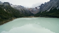 Aerial view of Emerald Lake in Ushuaia, Tierra del Fuego, Patagonia Argentina. Turquoise water lake in the mountaintop, surrounded by rocky peaks and forest that reflect in the glacier water.