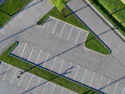 Aerial view of empty parking lot  with grass isles