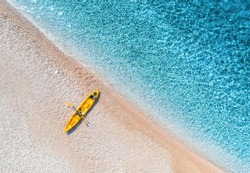 Aerial view of empty sandy beach with yellow canoe, sea coast with transparent blue water in sunny bright day in summer. Travel in Croatia. Top view of boat. Landscape with kayak at sunset. Travel