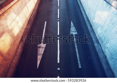 Aerial view of empty two lane road with opposite direction arrows