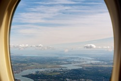 Aerial view of England and the River Thames from an airplane window with nice blue sky and clouds.